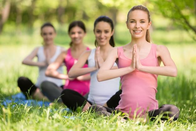 Groep jonge zwangere vrouwen die ontspanningsoefening doen.