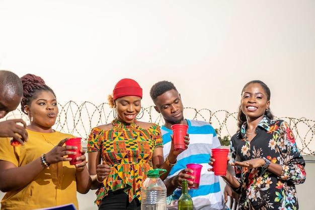 Groep jonge zwarte volwassenen die een feest geven, veel plezier hebben, een reüniefeest