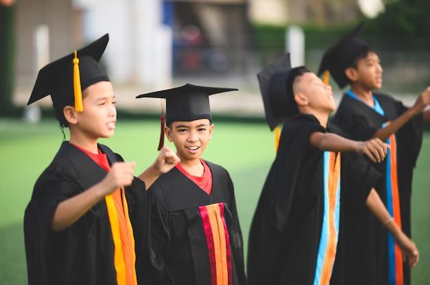Groep jongens zijn blij op hun afstuderen dag op school