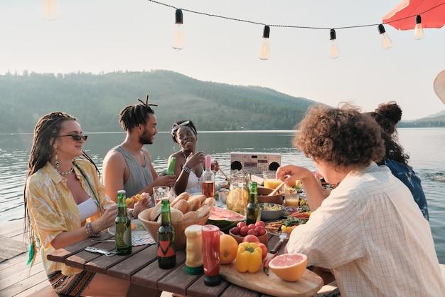 Groep jongeren aan tafel zitten en met elkaar praten tijdens het vakantiediner op een pier