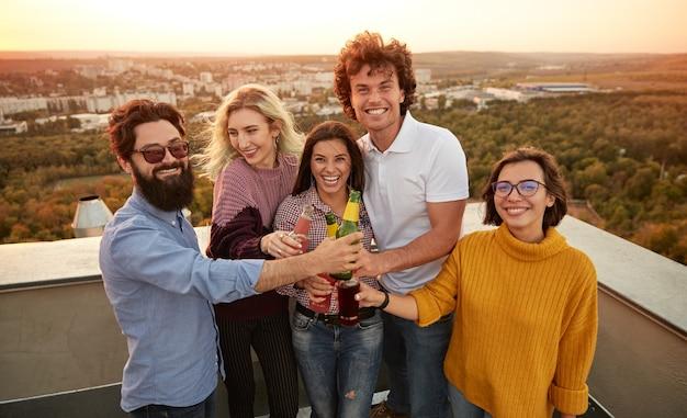 Groep jongeren bier drinken en samen ontspannen op het dak