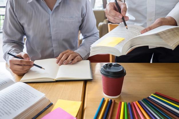 Groep jongeren die bestuderend nieuwe les aan kennis in bibliotheek leren tijdens het helpen van het onderwijs van de onderwijsvriend voor examen, de tienerjarenconcept van de de vriendschapstiener van de jeugdcampus voorbereidingen treffen