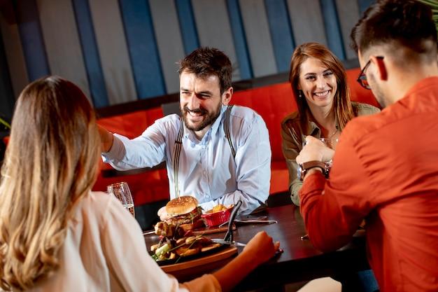 Groep jongeren die diner in het restaurant hebben