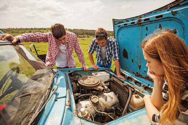Groep jongeren die een auto herstellen