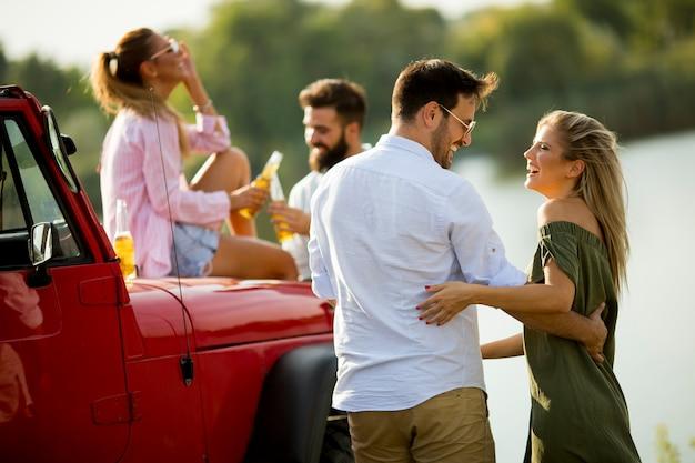 Groep jongeren die en pret drinken door auto openlucht bij hete de zomerdag