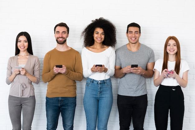 Groep jongeren die hun mobiele telefoons houden