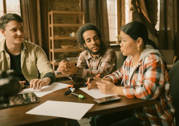 Groep jongeren die in bureau samenwerken