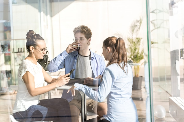 Groep jongeren die koffie drinken en hun mobiele telefoon bij coworking met behulp van
