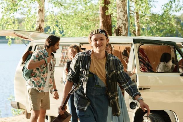 Groep jongeren die met de auto in het bos gaan kamperen