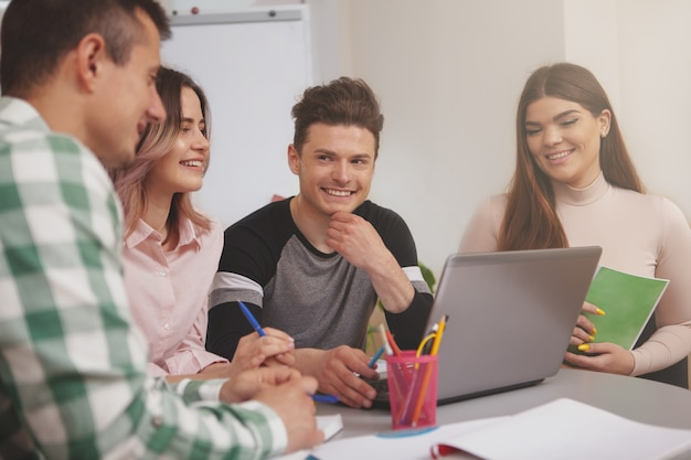 Groep jongeren die samen bij universiteitsklaslokaal bestuderen