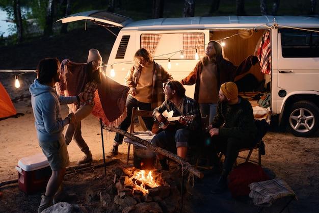 Groep jongeren die samen dansen rond het vuur tijdens het kamperen in het bos