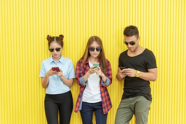 Groep jongeren die smartphone op muur gebruiken. netwerkverbindingstechnologie.