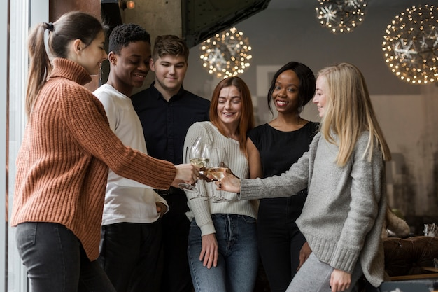 Groep jongeren die wijnglazen roosteren