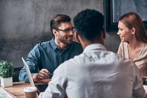 Groep jongeren in slimme vrijetijdskleding die zaken bespreken terwijl ze op kantoor werken