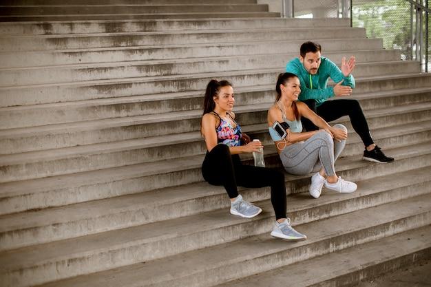 Groep jongeren rusten tijdens de training met een fles water in de stedelijke omgeving