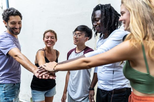 Groep jongeren uit verschillende etnische groepen die hun hand samenstellen