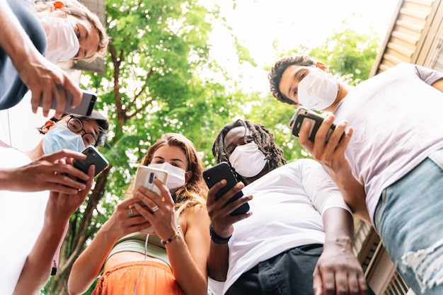 Groep jongeren van verschillende etnische groepen permanent samen met een mobiele telefoon in de hand dragen van beschermende maskers