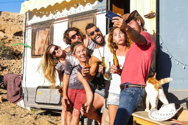 Groep jongeren vrienden nemen selfie foto met behulp van mobiele telefoon buiten caravan. groepeer mensen die grappige gezichten maken en een bierflesje vasthouden terwijl ze een selfie maken.