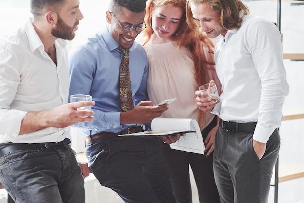 Groep kantoormedewerkers die naar de telefoon van de zwarte man kijken, hebben een gesprek