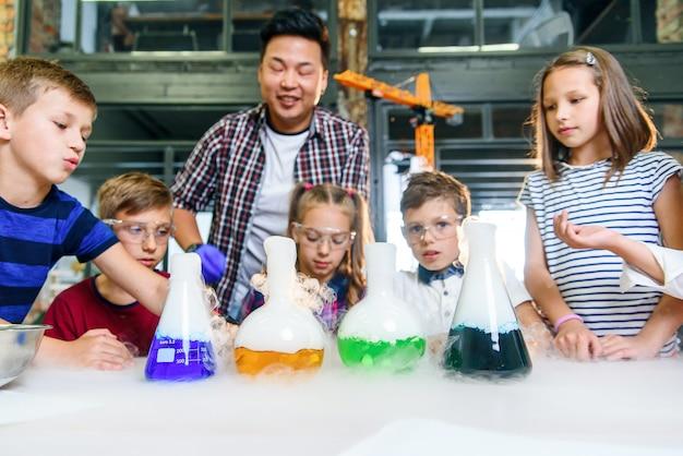 Groep kaukasische schoolkinderen in chemisch laboratorium. leerlingen stoppen met kleurrijke vloeistoffen droogijs in de kolven, wat een intensieve verdamping veroorzaakt.