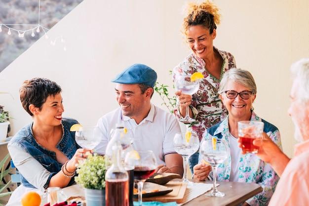 Groep kaukasische vrolijke gelukkige mensen die samen wat wijn drinken en plezier hebben in vriendschap Premium Foto
