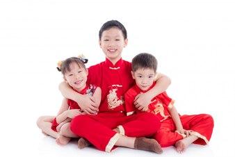 Groep kinderen die Chinese traditionele kostuumzitting op de vloer dragen