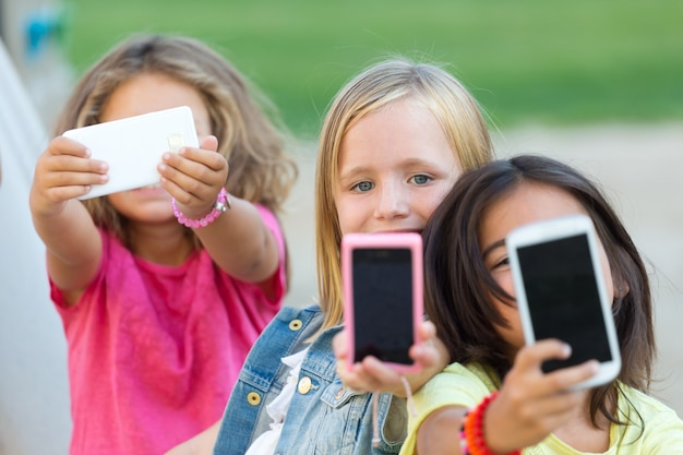 Groep kinderen die een selfie in het park nemen.