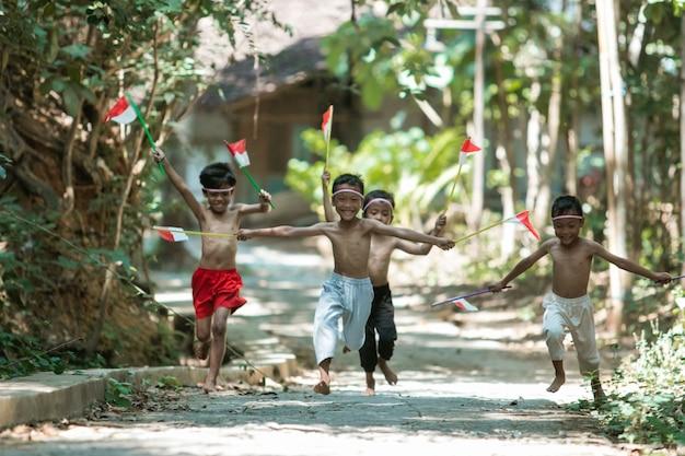 Groep kinderen die zonder kleren rennen terwijl ze vlaggen vasthouden
