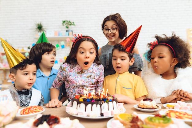Groep kinderen gaat kaarsen op taart blazen.