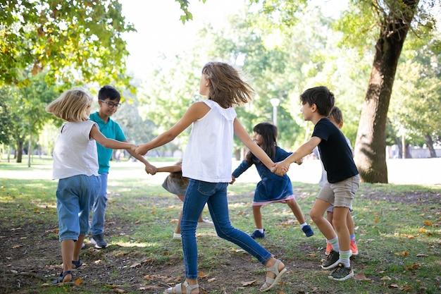 Groep kinderen hand in hand en dansen rond, genieten van buitenactiviteiten en plezier maken in het park. kinderfeestje of vriendschapsconcept