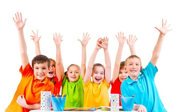 Groep kinderen in gekleurde t-shirts zitten aan een tafel met opgeheven handen.