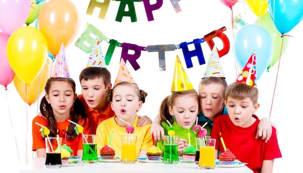 Groep kinderen in kleurrijke shirts blaast kaarsen op het verjaardagsfeestje - geïsoleerd op een witte.