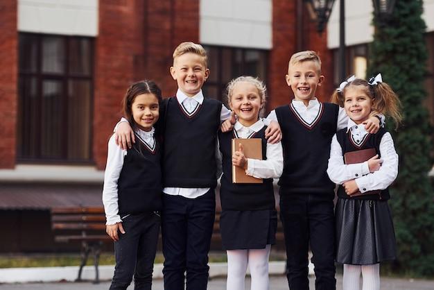 Groep kinderen in schooluniform dat buiten samen is in de buurt van het onderwijsgebouw.