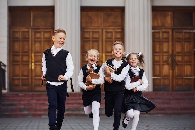 Groep kinderen in schooluniform dat samen buiten loopt.