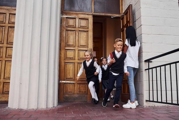 Groep kinderen in schooluniform die door de deur uit een gebouw rennen.