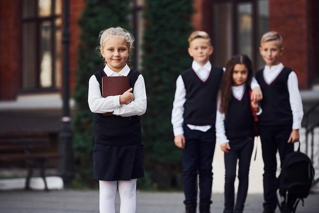 Groep kinderen in schooluniform poseren voor de camera buiten samen in de buurt van onderwijsgebouw.