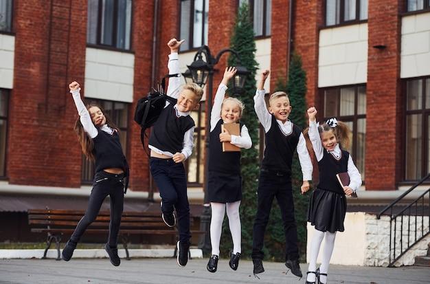 Groep kinderen in schooluniform springen en plezier buitenshuis samen in de buurt van onderwijsgebouw.