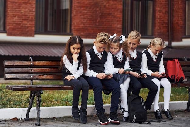 Groep kinderen in schooluniform zit samen op de bank buiten in de buurt van het onderwijsgebouw.
