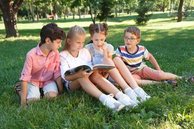 Groep kinderen lezen samen een boek buiten in het park