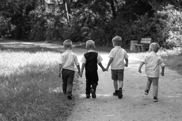 Groep kinderen lopen langs pad naar camera in park