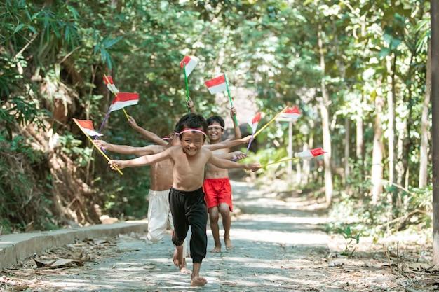 Groep kinderen rennen zonder kleren achter elkaar aan met vlaggen vast