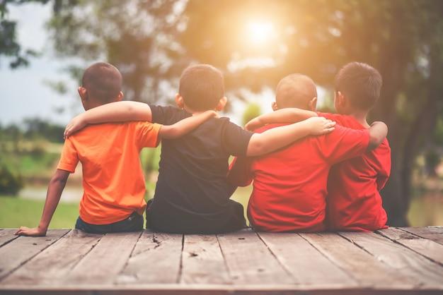 Groep kinderen vrienden arm rond elkaar zitten