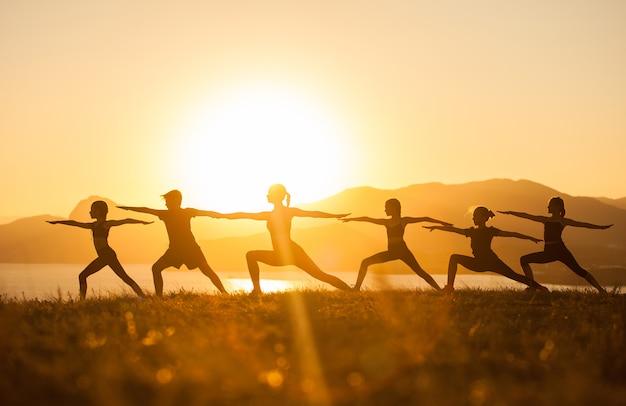 Groep kinderen zijn bezig met yoga met een trainer op de oceaan.