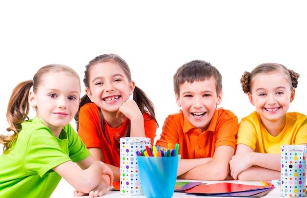 Groep kinderen zitten aan een tafel met stiften, kleurpotloden en gekleurd karton
