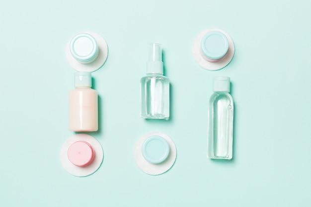 Groep kleine flessen voor reizen op blauw. copyspace r ideeën. plat lag samenstelling van cosmetische producten. bovenaanzicht van crème containers met wattenschijfjes