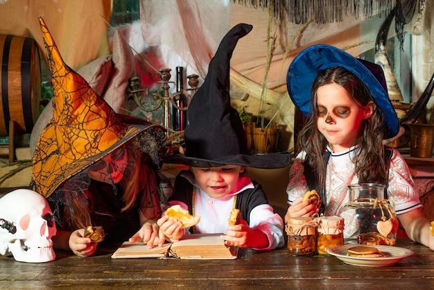 Groep kleine heks met een pompoen en snoep verraste groep kleine zombie in halloween kostuum e...