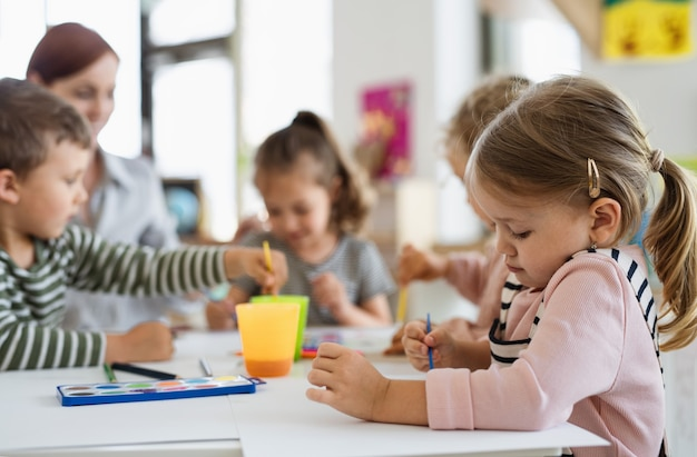 Groep kleine kleuterschoolkinderen met leraar binnenshuis in klaslokaal, schilderen.