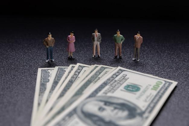 Groep kleine zakenlieden die zich op muntstukken bevinden