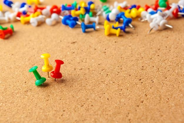 Groep kleurrijke duwspelden op cork prikbord