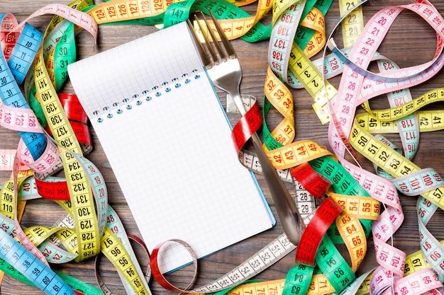 Groep kleurrijke maatregelenbanden, open notitieboekje en vork op houten met lege ruimte voor uw idee.